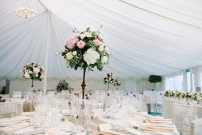 tall table arrangements of cream pink and burgundy flowers by Your London Florist
